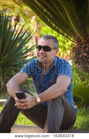 A young man on vacation at the beach resort . Man enjoying holiday sitting under a palm tree and smiling