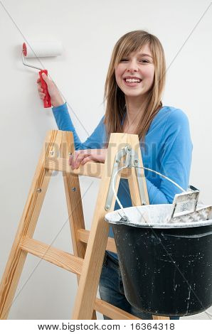 Home improvement. Young woman painting wall with paint roller