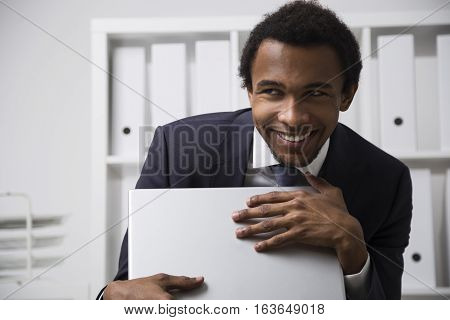 Portrait of a very shy African American office clerk working in a white office smiling and grasping his laptop as a treasure. Concept of shyness and social awkwardness