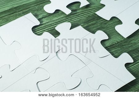 The concept of logical thinking. Logical conundrum. White jigsaw puzzle on a wooden background. Business concept with white jigsaw puzzle on green wooden background. Placing missing a piece of puzzle.