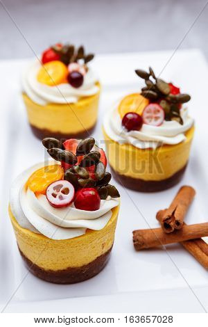 Delicious pumpkin cupcakes on white dish with cinnamon sticks