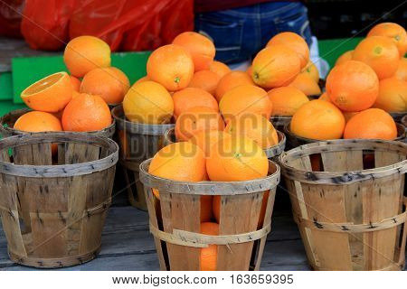 Several wood baskets, two empty and others filled with ripe, juicy oranges.