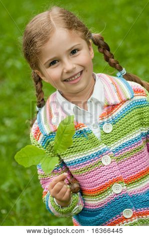 Little girl and young plant of a oak