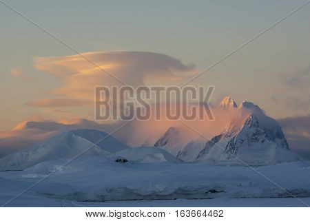 lenticular cloud at sunset over the mountains of the Antarctic Peninsula