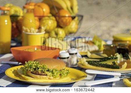 Summertime. A picnic on the beach. Burgers and pitas vegetables and fruits. Selective focus.