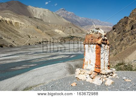Border stone at the river bank. Entrance to Mustang area from village of Kagbeni in Nepal.