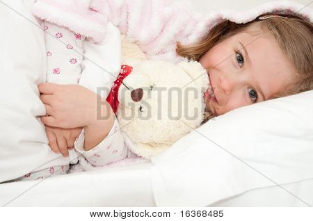 Little girl in bed hugging no-name teddy bear