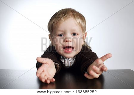 photo of little boy gesturing sitting at table