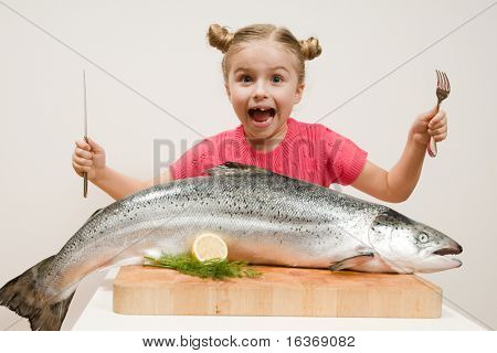Little girl and big fresh fish - healthy eating seafood