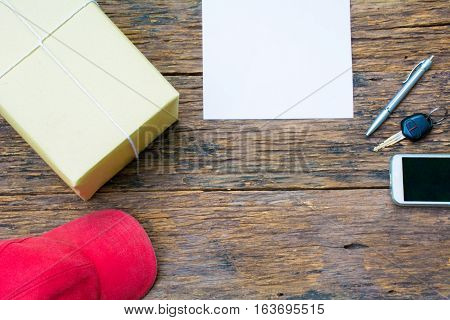 The red cap, parcel post, white paper, pen, key of car and smart phone on old bark