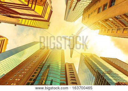 Airplane flying over modern skyscrapers on Hong Kong, Central District with sun light of sunset sky. Glass high-rise facade. Concept of transport, travel and business. View from bottom skyscrapers.