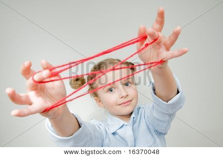 Creative mind - little girl playing cats cradle game