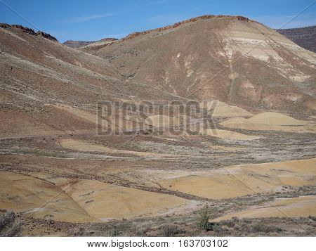 A dirt road winds through the colored mounds and hills of the Painted Hills Unit of the John Day Fossil Beds in Eastern Oregon on a winter day.