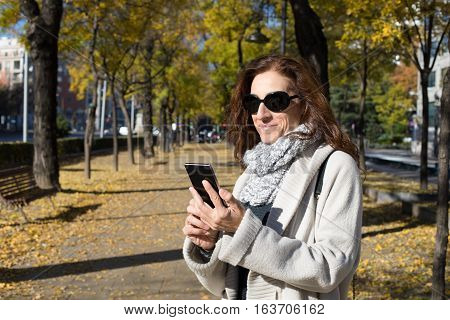 happy woman with grey cardigan and scarf black sunglasses watching smartphone in urban street in Madrid city with trees in autumn