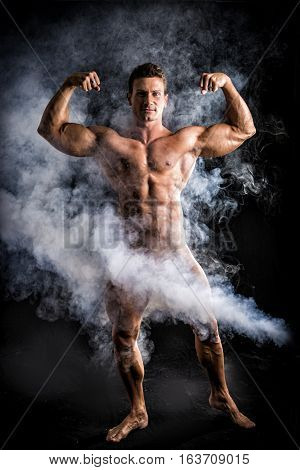 Totally naked male bodybuilder with smoke hiding genitalia, looking at camera, on dark background