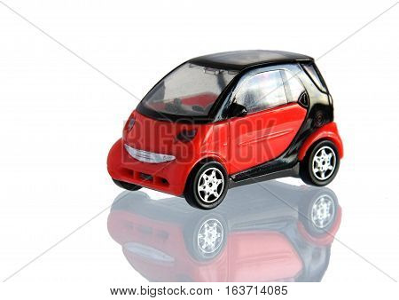 Small red toy car isolated on white with reflection