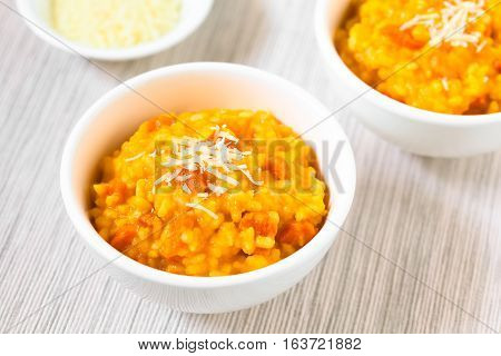 Fresh homemade carrot risotto made with pureed carrot and roasted carrot pieces garnished with grated cheese photographed with natural light (Selective Focus Focus in the middle of the risotto)