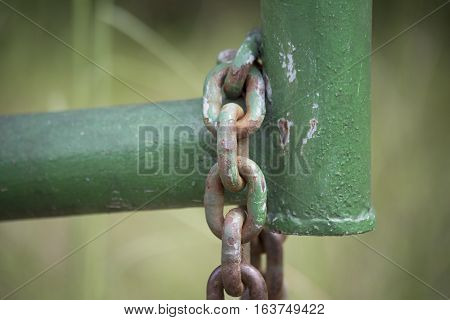 Chain hanging off of a green property gate