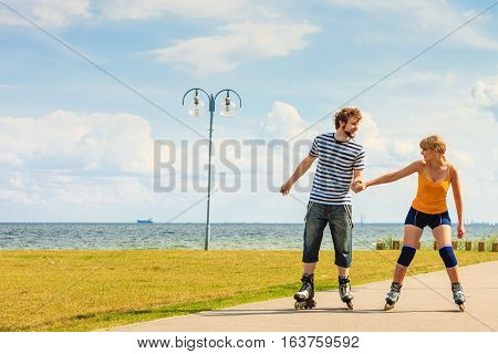 Summer active lifestyle people and friendship concept. Young fit couple on roller skates riding outdoors on sea coast woman and man rollerblading together on the promenade