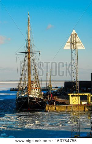 Black fishing boat is docked while the waves shower. fishing trawler