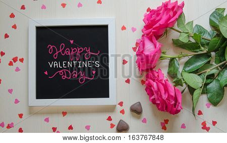 St Valentine's Day vintage composition of white photo frame with love quote, pink roses bouquet and paper hearts. Top view