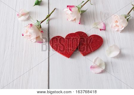 Valentine background with pink rose flowers petals and handmade wooden glitter hearts on white rustic wood. Happy lovers day mockup, copy space