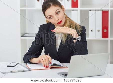 Beautiful thoughtful business woman sitting at office workplace looking into the distance. Serious business and partnership job offer financial success certified public accountant concept