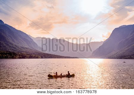 Family rowing in canoe boat on beautiful lake Bohinj at sunset, located in the Bohinj valley of Julian Alpsin in Triglav national park, Slovenia.
