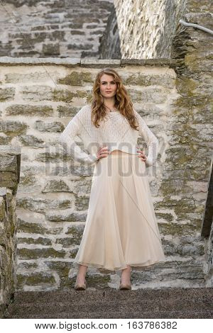 Caucasian white female model and brick stone. Beautiful girl long red hair beige skirt and cardigan. Woman standing on the stairs in old town limestone walls background