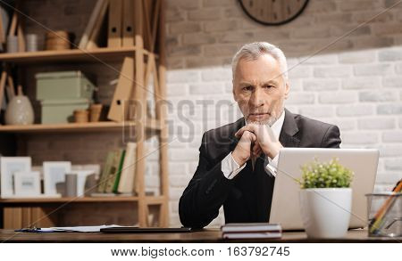 Some issues must be taken care of. Professional doubtful mature manager sitting at his desk and trying putting some thought into important problems