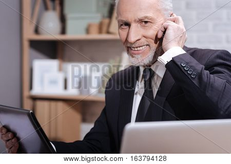 Project will be a success. Positive convincing mature businessman discussing debatable point of the contract with his colleague while holding a phone and using his tablet