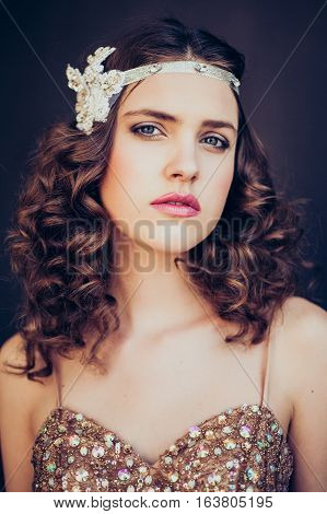 Fashion photo of beautiful girl wearing sparkling evening dress. Professional make-up and hairstyle. Perfect skin. Fashion photo. Gatsby style.