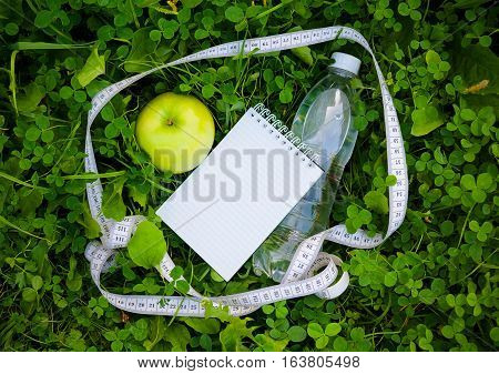 Bottle of water measuring tape and apple on green grass