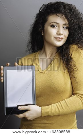 Going to work. Amazing girl with enigmatical smile wearing yellow cardigan holding black tablet in her hands while looking at camera, isolated on grey background