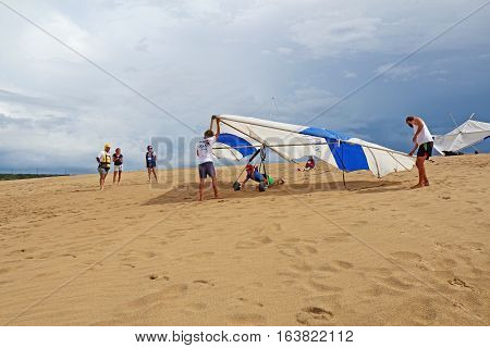 NAGS HEAD NORTH CAROLINA - JULY 28 2013: Student does a flight check with instructors from the Kitty Hawk Kites Hang Gliding School on the sand dunes of Jockeys Ridge State Park on the Outer Banks.