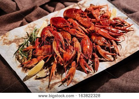 Well done. Tasty crayfishes with lemon lying on pita in restaurant while being put together on a table.