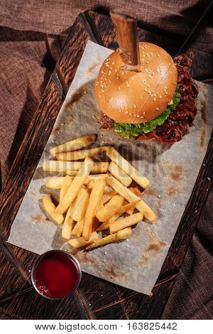 Looks how it tastes. Top view of tasty big burger and French fries standing on a wooden tray while being served with pita and sauce in restaurant.