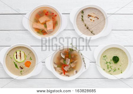 Variation of tasty restaurant hot dishes flat lay. Top view on white wooden table with set of different soups. Worldwide cuisine, healthy food, buffet, lunch, menu concept