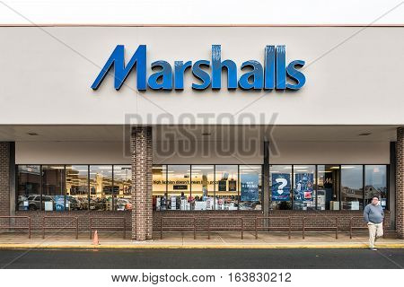 Fairfax, USA - November 30, 2016: Marshalls storefront with blue sign and person walking by entrance of store