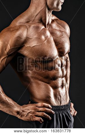 Beautiful naked male torso against black background