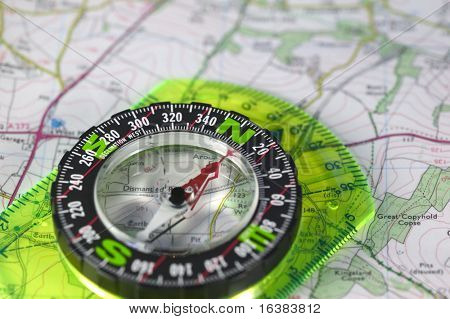 A compass with marked degrees and a north heading on a paper map