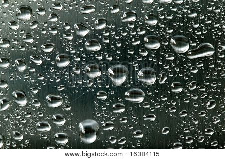 Water droplets on a brushed steel surface.