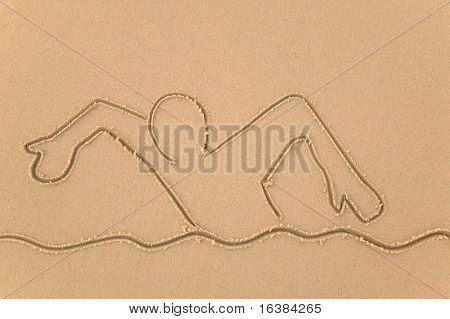 Sand drawing of a person swimming.