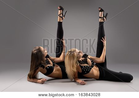 Sexy slim blonde and brunette in black leggings, brassiere with silver rhinestones and high heels lying with legs up studio shot