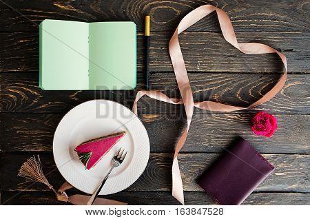 Valentine's day flat lay. Heart shaped ribbon flower raspberry cake slice notepad. Dark wooden table