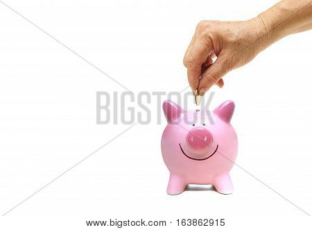 Old hand putting a golden coin into a pink piggy bank / saving money for retirement concept