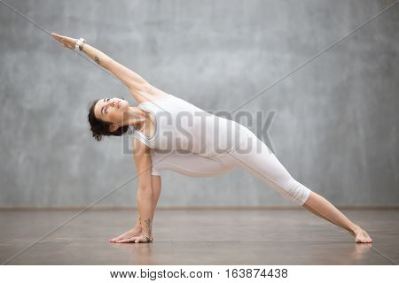 Portrait of beautiful young woman wearing white sportswear working out against grey wall, doing yoga or pilates exercise. Standing in Utthita parsvakonasana, extended side angle pose. Full length