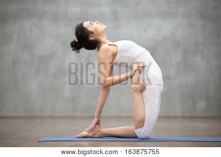 Side view portrait of beautiful young woman wearing white sportswear working out in fitness center against grey wall, doing yoga or pilates exercise. Variation of ustrasana, camel pose. Full length