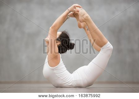 Side view portrait of attractive young woman with tattoo on her foot meaning Wild kitty working out in fitness club or at home, doing yoga or pilates exercise. Dhanurasana, Bow pose. Full length