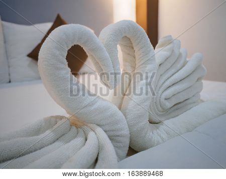 white pillow and blown pillow and fold the towel as a swan kiss each other on the white bed in bedroom